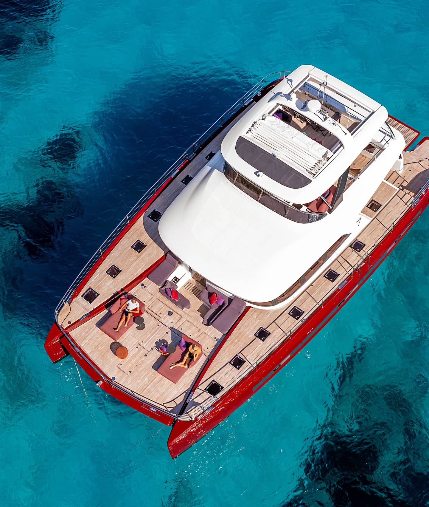 Un catamarano Lagoon rosso fuoco, staziona in una baia dall'acqua turchese mentre una coppia prende il sole a prua.