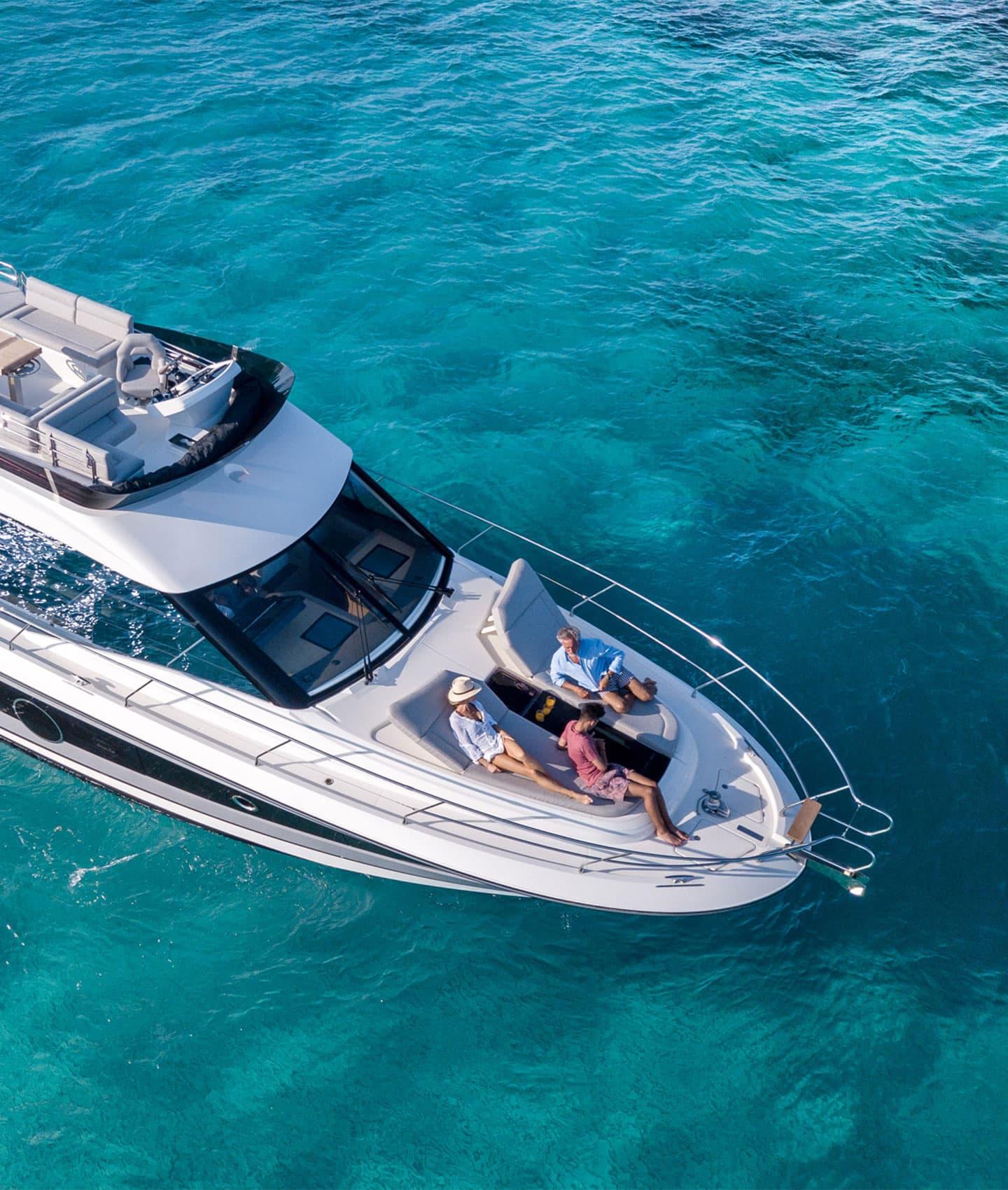 Famiglia si gode la vita sulle sedute a prua di uno yacht a motore Beneteau, stazionato in un mare turchese.