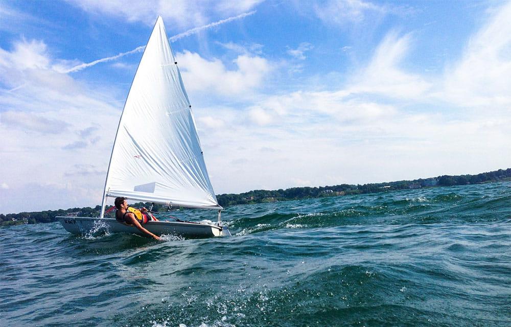 Un uomo naviga a vela su una piccola barca a vela, sfiorando l'acqua con una mano.