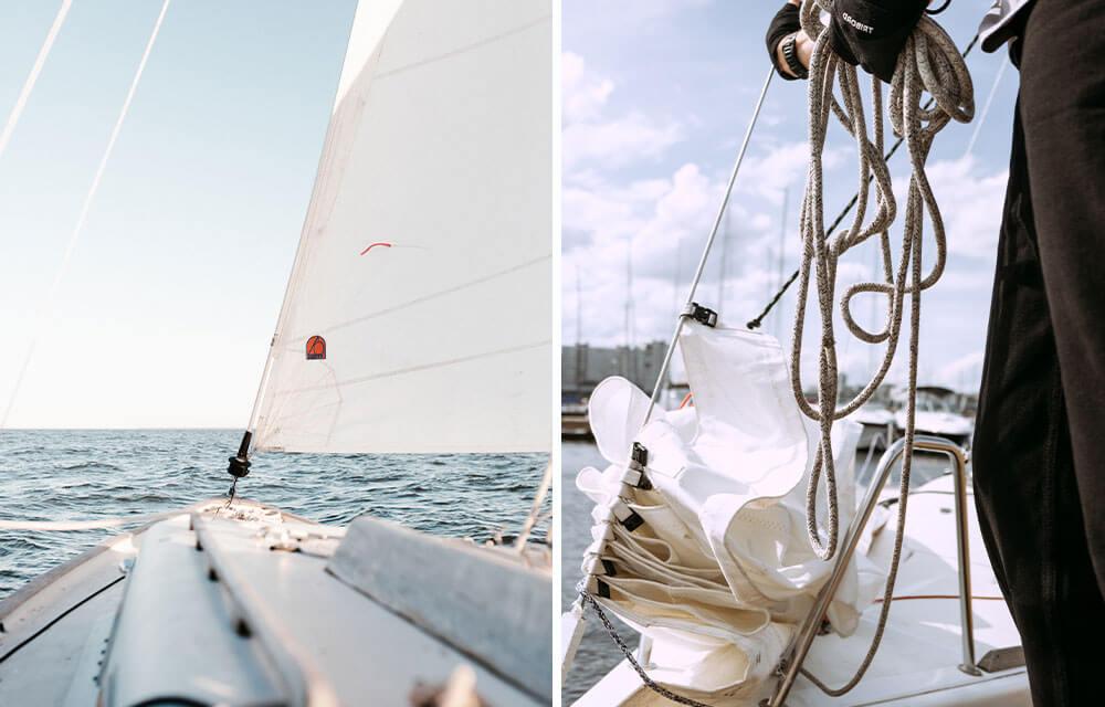 Un dettaglio della prua di una barca a vela, con il mare all'orizzonte a sinistra e una cima di una vela di una barca attorcigliata a destra.