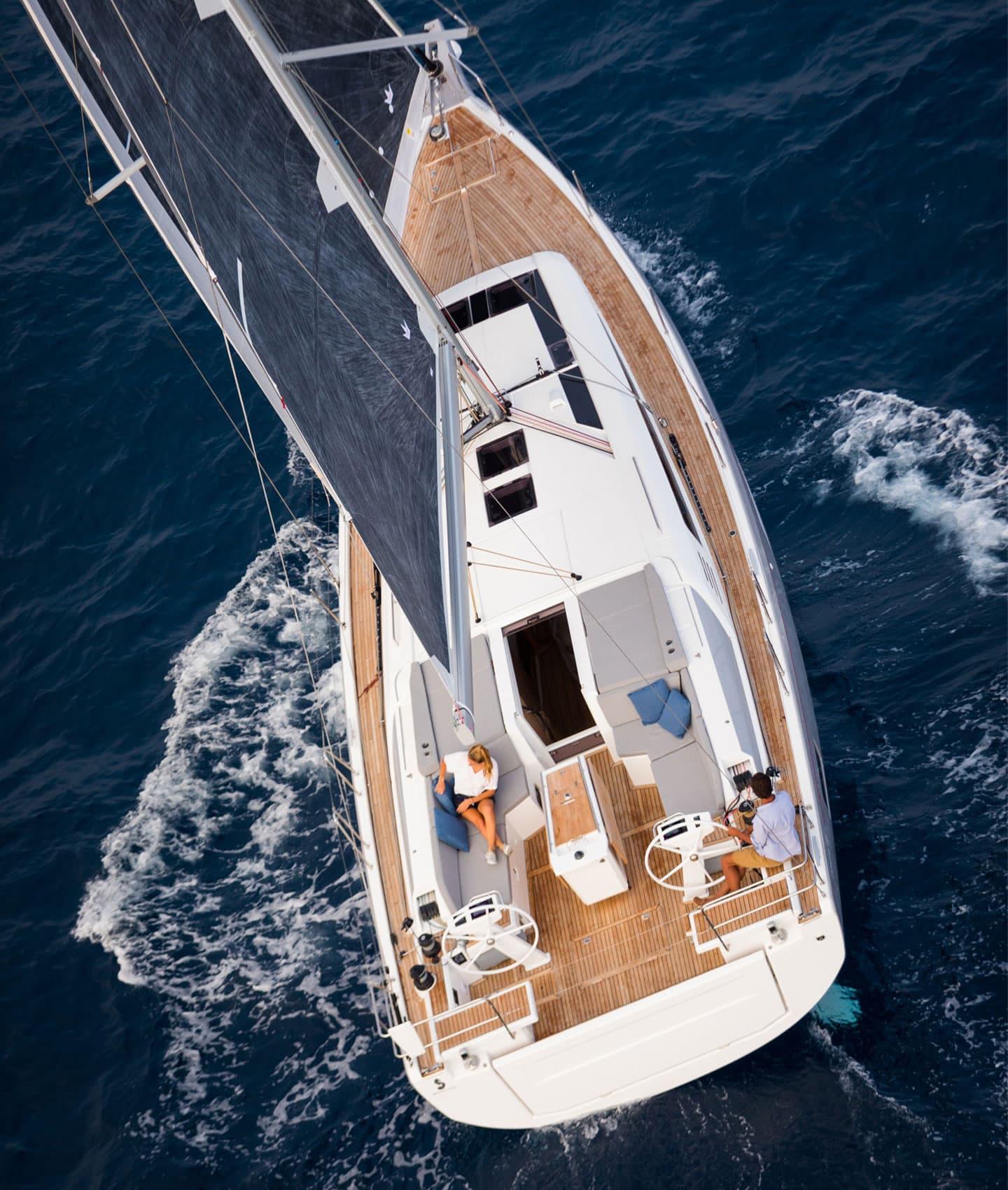 Una vista dall'alto di una coppia che naviga su una barca a vela del gruppo Beneteau in mare aperto