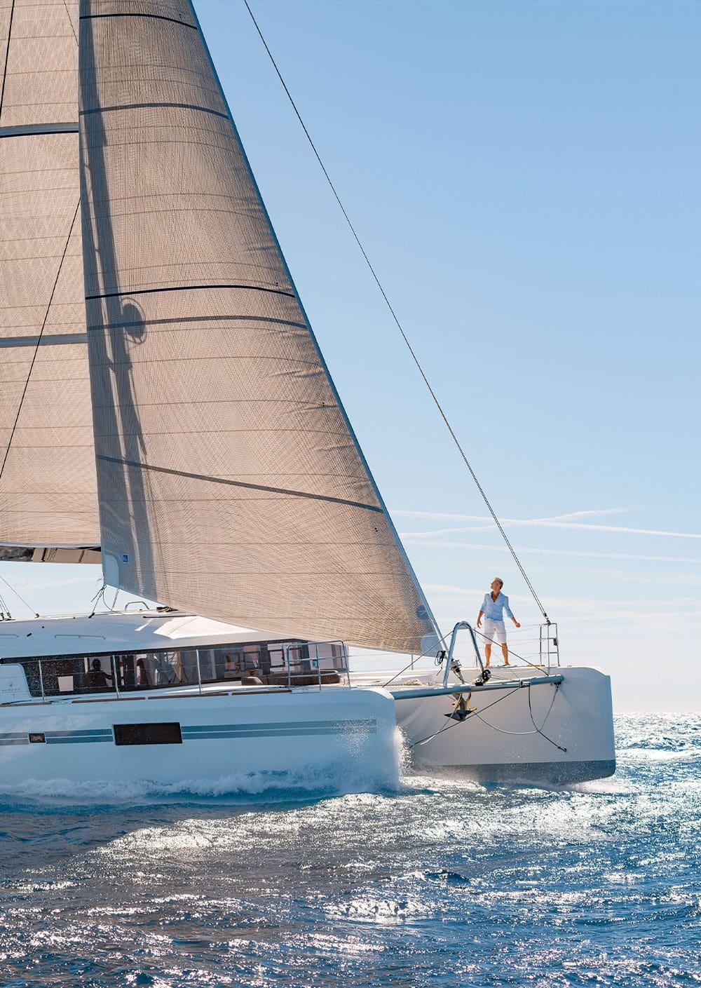 Un uomo a prua di un catamarano Lagoon, guarda la vela maestosa della sua barca a vela mentre il mare si infrange sulla carena della barca.