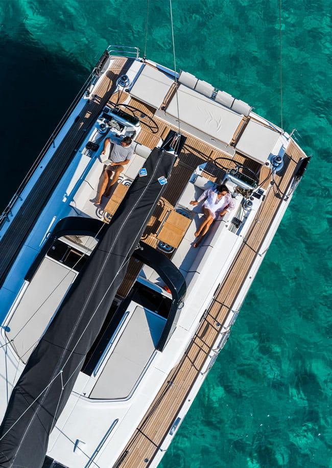 Una coppia stesa sui lettini a poppa di uno Yacht a Vela, si gode la vita rilassandosi sulla barca a vela.