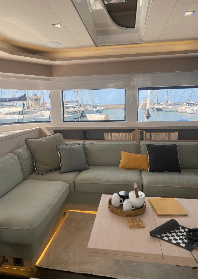 L'interno del catamarano Lagoon 55 con un divano verde salvia e un tavolino da caffè con vari oggetti decorativi