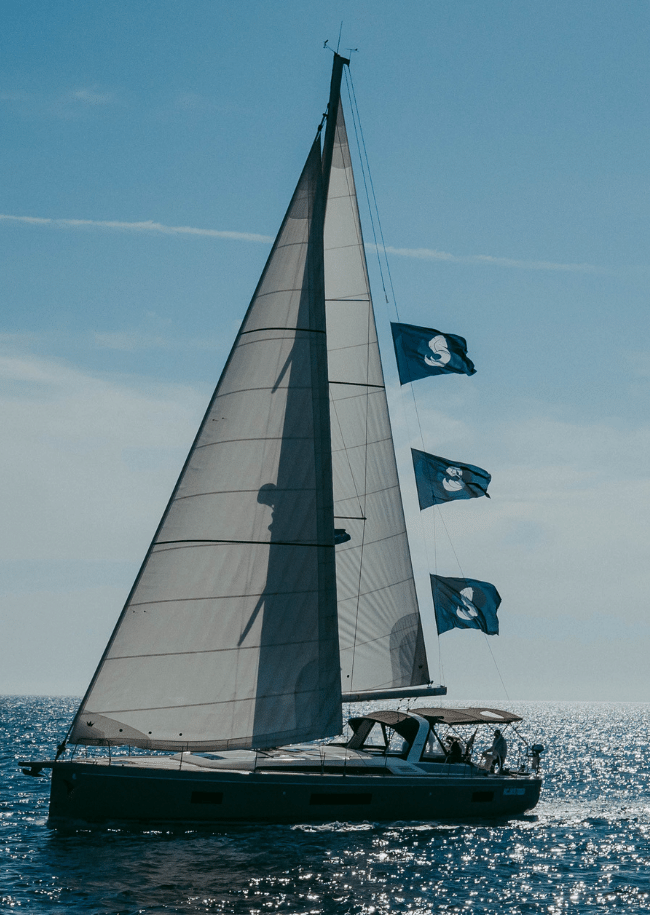 Una barca a vela in navigazione con le vele spiegate, e con le bandiere del cantiere Beneteau issate