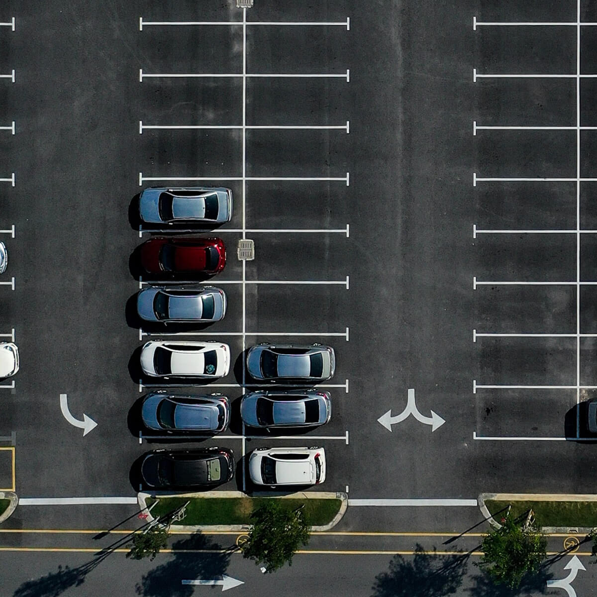 Photo of an elevated view of a parking lot with cars and empty spots