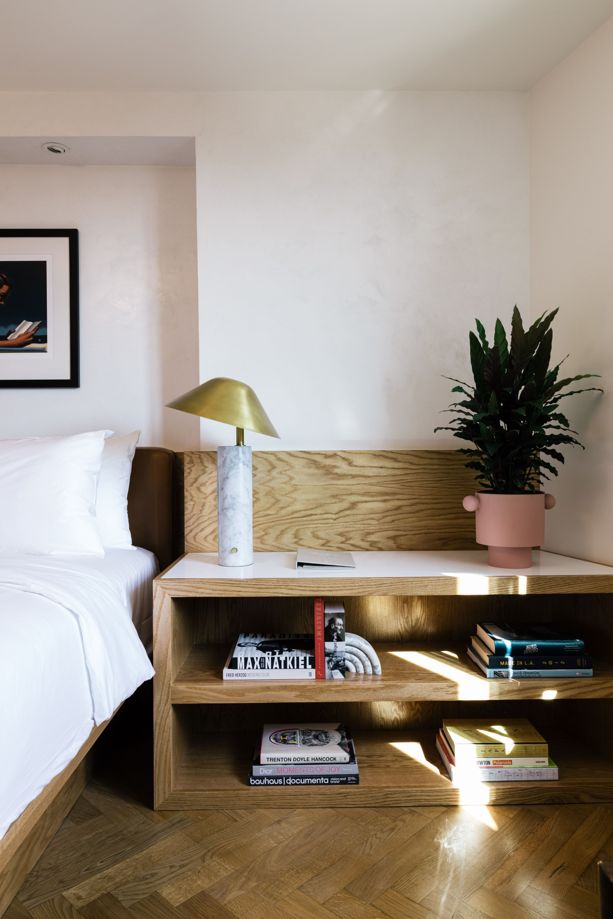 Bedside table with books, lamp, plant and sunlight