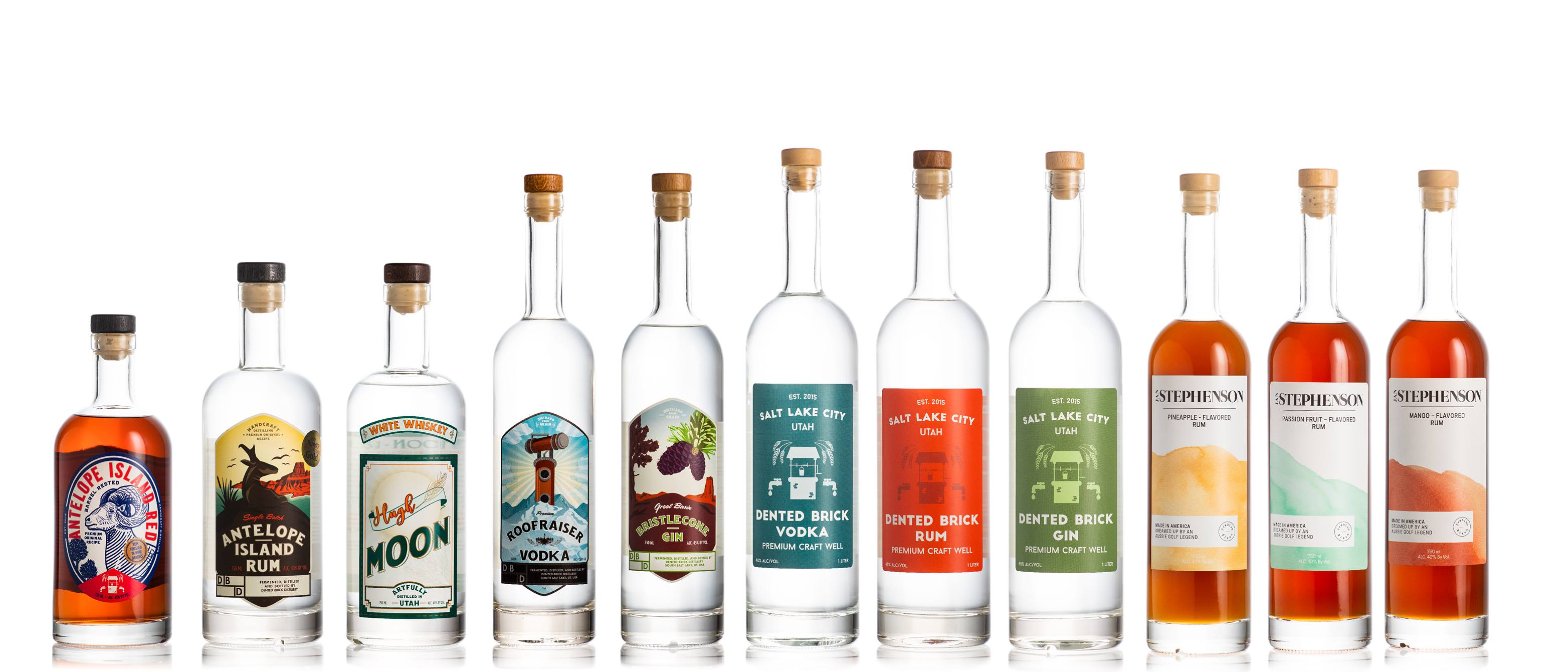 Row of Dented Brick Distillery spirits bottles, including rum, vodka, and gin