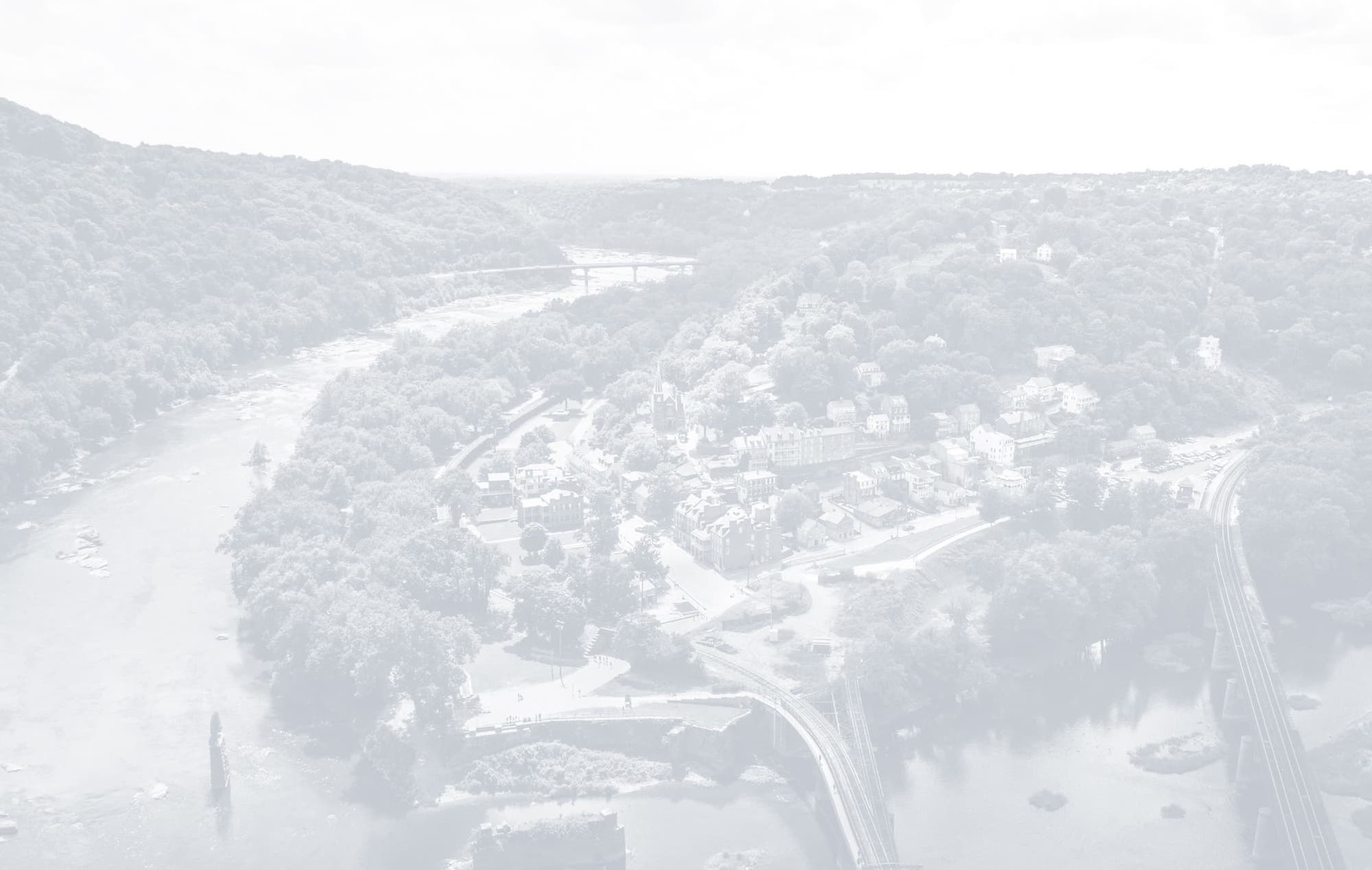 Panoramic shot of a river curving around a city's downtown area.
