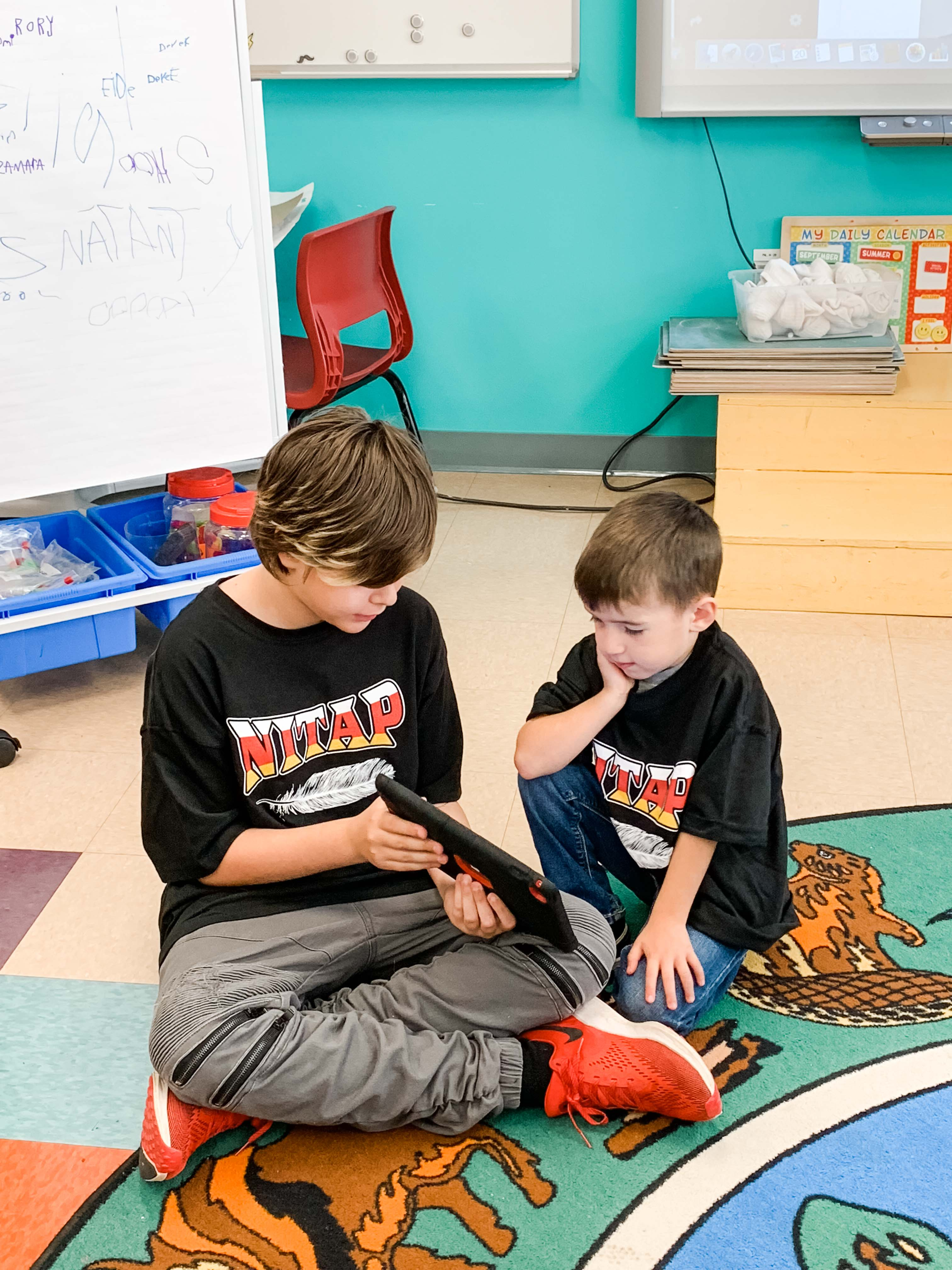 Two Mi'kmaq boys reading from tablet