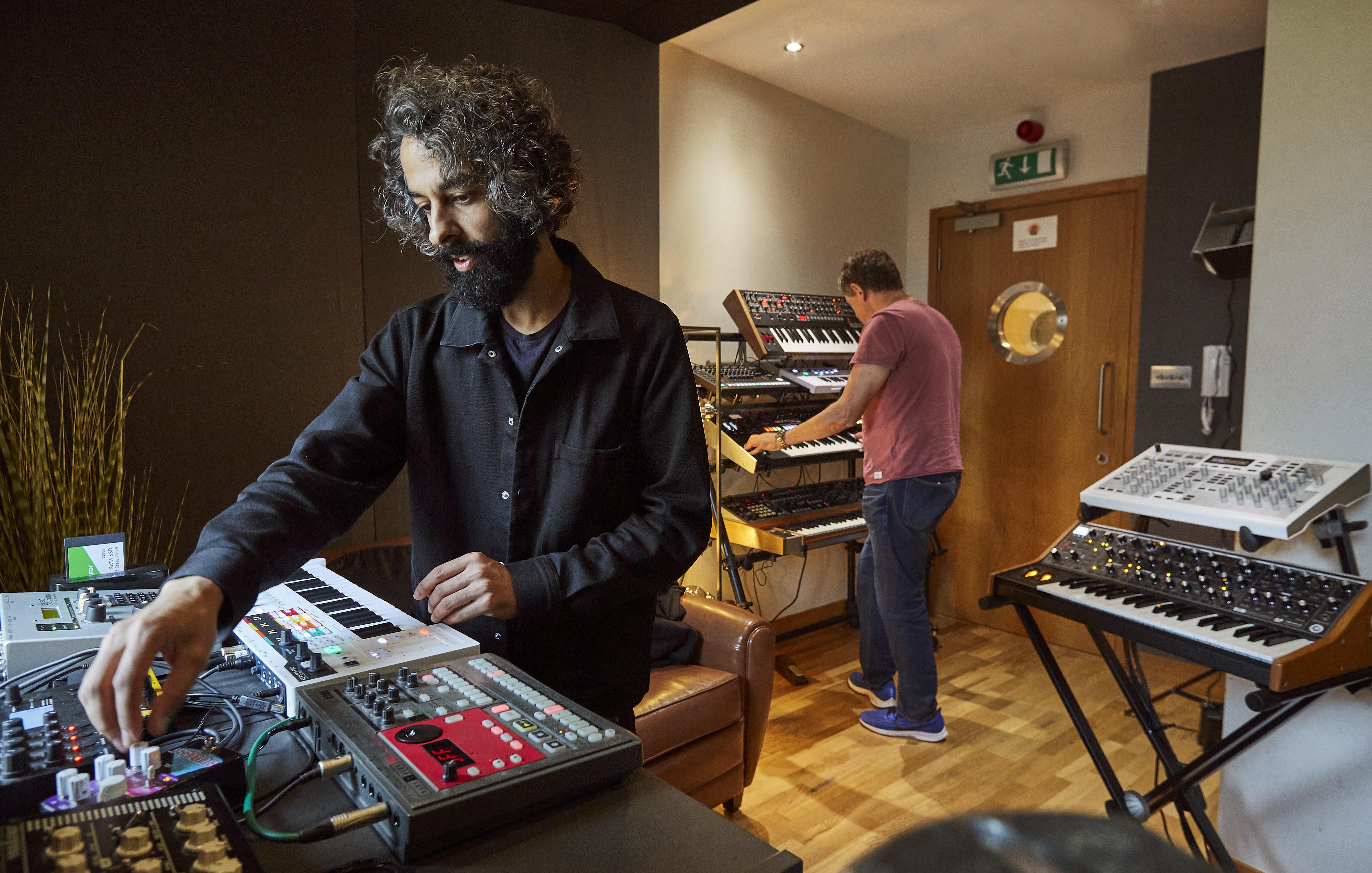 Two men using keyboards playing audio