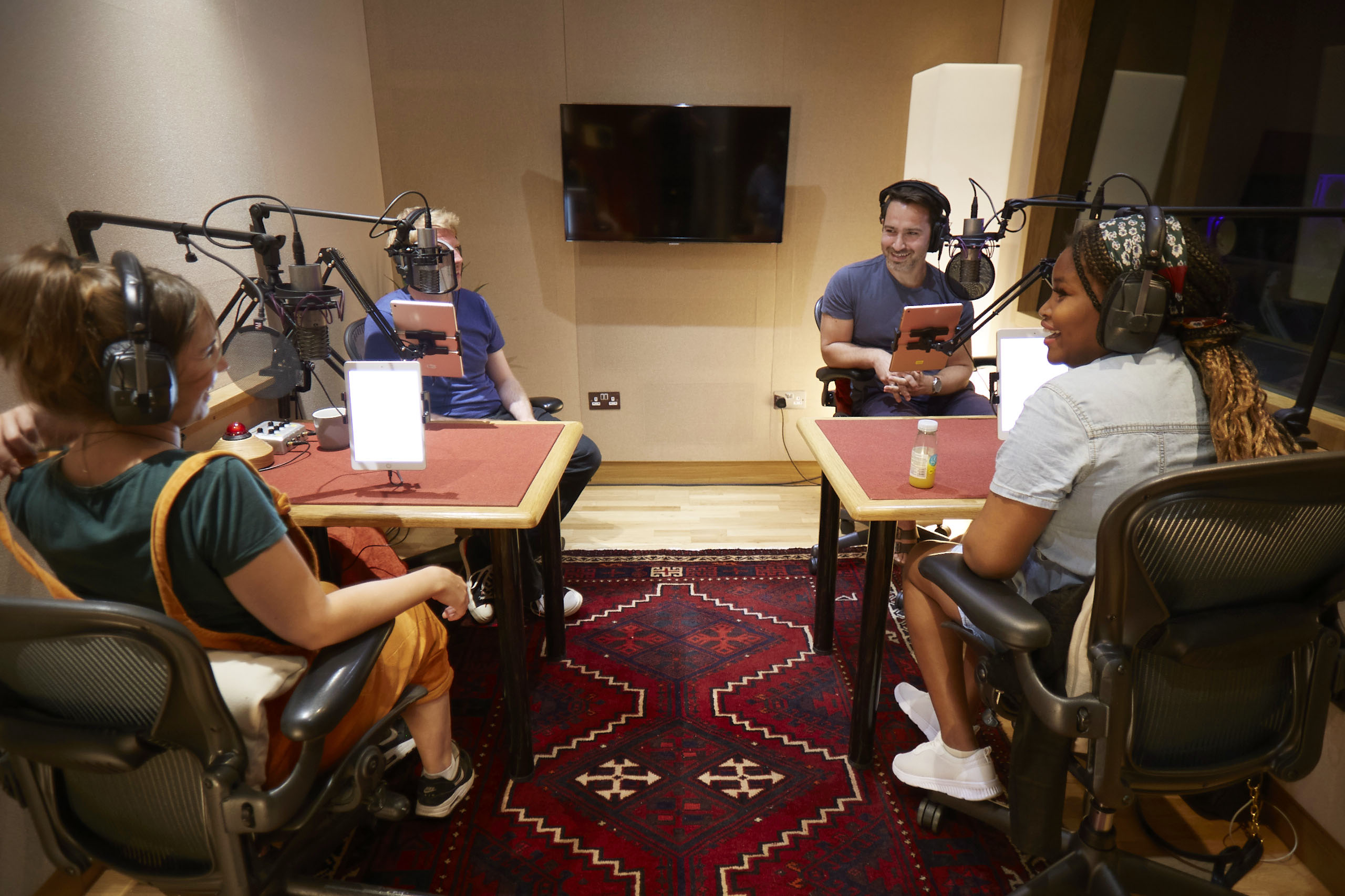Four people recoding audio in a studio