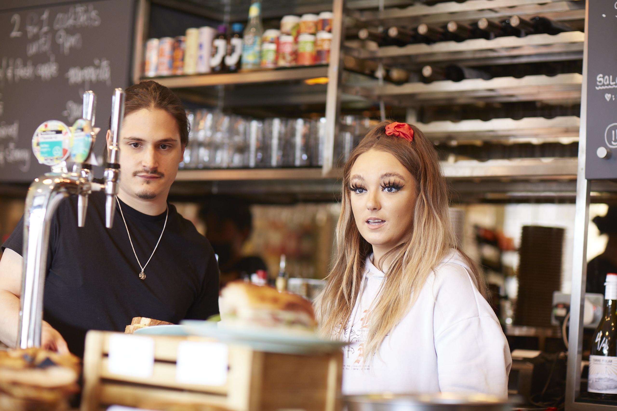 Two people behind the Vinyl Cafe var