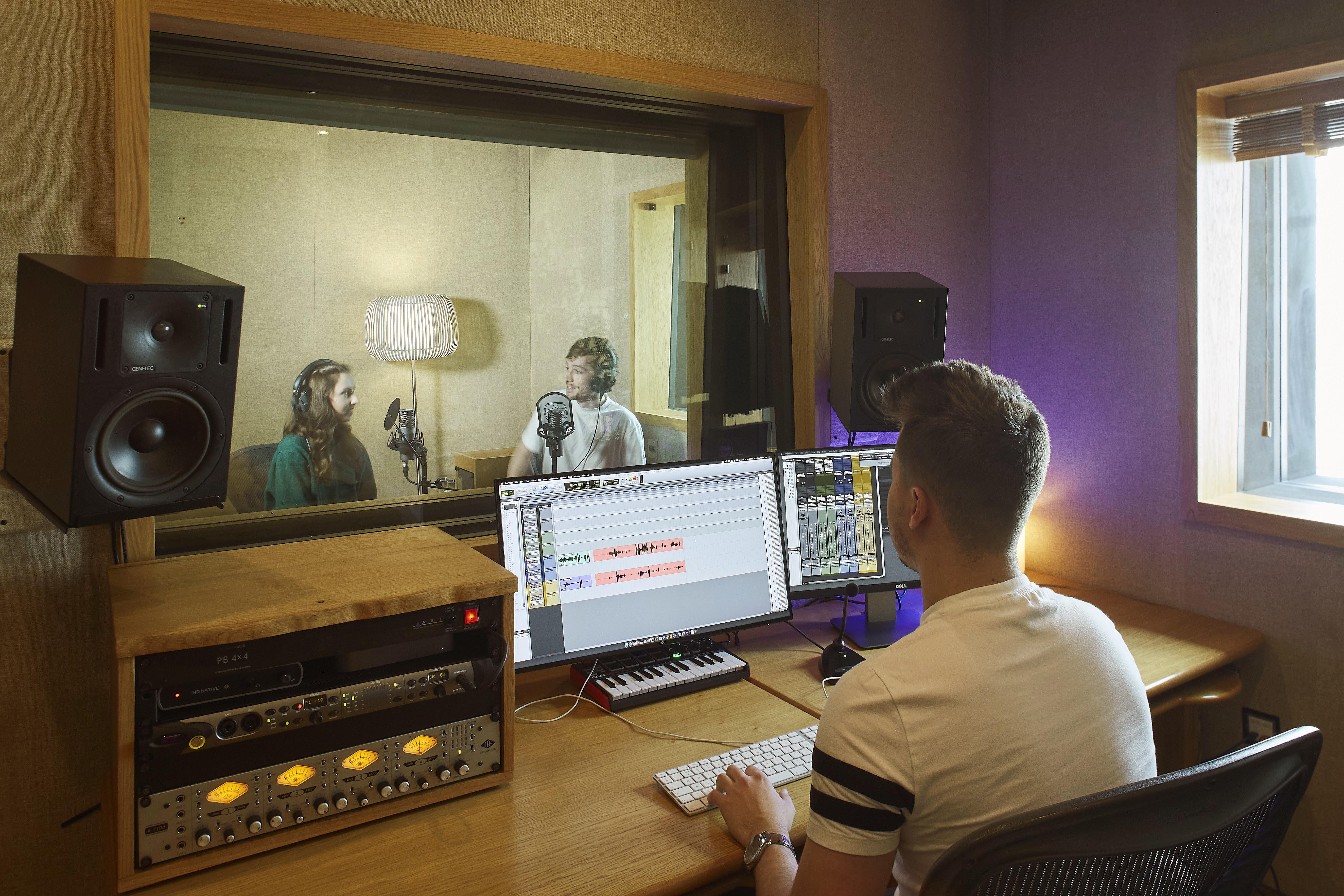 Three people recording audio in a studio