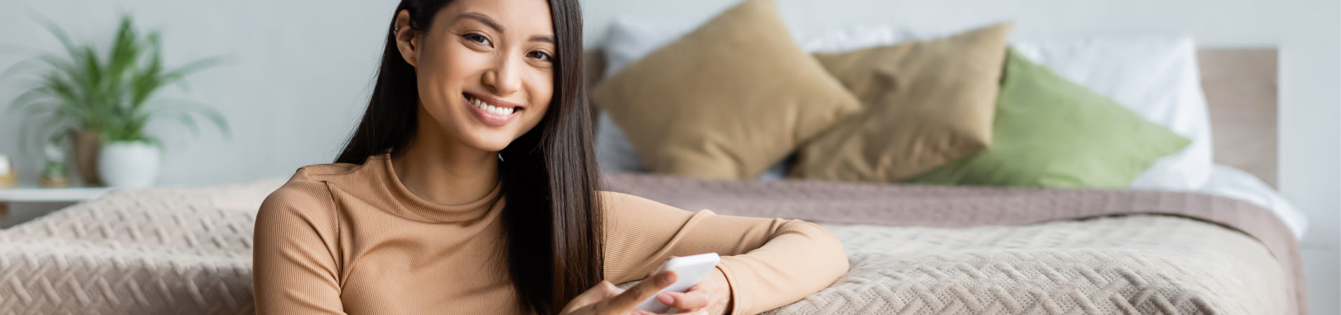 Young woman smiling, sitting in front of her bed while holding her smart phone in her hand.